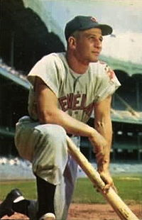Baseball player Al Rosen, a 29-year-old blond man, is pictured in the white uniform of the Cleveland Indians, kneeling with a baseball bat, circa 1953.