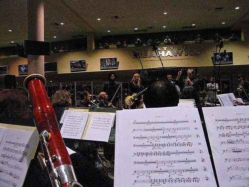 A photo of rock band Alice in Chains in a rehearsal. The photo is taken from inside the orchestra which is playing with the band. Music stands and a bassoon can be seen.
