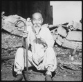 An old Korean man takes a rest on the street in front of destroyed buildings, in Seoul. - NARA - 530637.tif