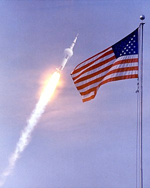 Apollo 11 launch framed by American flag.