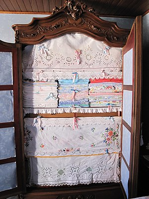 Linens - A French armoire with home linens arranged in a traditional manner, with embroidered dust covers over the shelves.