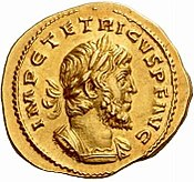 The obverse of a golden coin showing a bust Tetricus