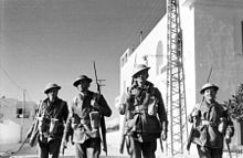 Soldiers wearing leather jerkins and helmets walk past whitewashed buildings with rifles slung