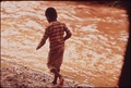 BOY WALKS ALONG BANKS OF CREEK POLLUTED BY EFFLUENT FROM NEIGHBORING STEEL MILLS - NARA - 545539.tif