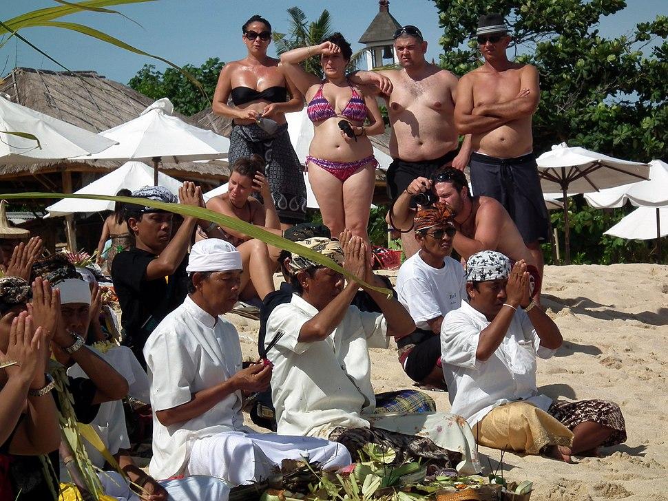 Bali religiös ceremoni på strand med turister