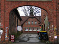 Biermannstraße 16, Celle, Gebäude der ehemaligen Celler Lederwerke, gemauerter Torbogen aus Klinker mit Blick auf das Gebäude mit Uhrturm, Aufschriften B16 bleibt ... dreckig.jpg