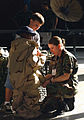 Brandon Hinton 6-year old son of US Air Force (USAF) Technical Sergeant (TSGT) Michael Hinton gets help from Senior Airman (SRA) Kristi Scott, as he dons a desert-camouflaged oversuit and other chemical warfare 030820-F-VG334-002.jpg