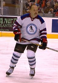 Bryan Trottier in a hockey jersey and holding a hockey stick, with ice skates on