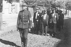 Vilna Ghetto - Lithuanian Nazi policeman with Jewish prisoners, July 1941