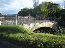 Arched bridge with metal railing. Sign showing River Parrett, Burrow Bridge.