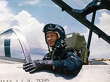 Aldrin sits in a cockpit of a grey plane with the canopy tilted open, looking off in the distance. He wears black leather gloves and a blue flight suit. Tinted goggles rest on his helmet, his oxygen mask hanging on the side