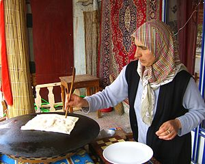 Göreme - Image: Central Anatolian Cafe Owner Flat Breadwith Beautiful Rug Hanging Goreme Cappadocia 2006