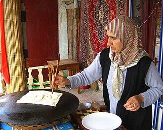 Göreme - Image: Central Anatolian Cafe Owner Flat Breadwith Beautiful Rug Hanging Goreme Cappadocia 2006