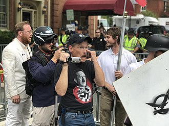 Alt-right - Protestors at the 2017 Unite the Right rally, which was promoted by the alt-right. One man carries the logo of Vanguard America, and another has a t-shirt praising German Nazi leader Adolf Hitler