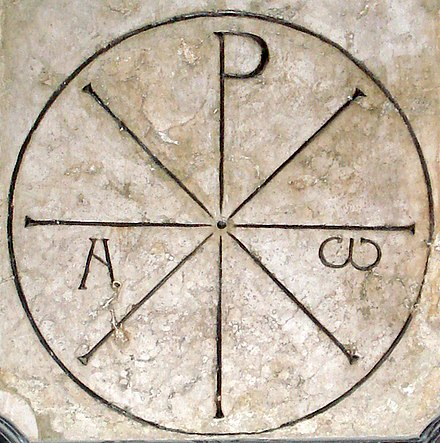 "The so-called ""Chrismon of Saint Ambrose"" (Chrismon Sancti Ambrosii), on display on the eastern wall of Milan Cathedral, a Chi-Rho combined with Alpha and Omega in a circle. According to Landulf of Milan (12th century), it was used by Saint Ambrose to introduce the catechumens to the mysteries of the Christian faith (whence it was called ""oracle"" or chresmos of St. Ambrose, written by Landulf as crismon, whence the later New Latin term for the Chi-Rho symbol). Chrismon Sancti Ambrosii.jpg"