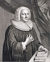 A baroque clergyman in minister's ornate, standing behind a table on which he touches a book with his left hand, while pointing towards his heart with the righ hand