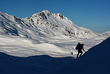 A hiker ascends a snowfield, with the sunlit slopes of a large, snowy mountain in the background