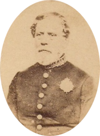 Sepia toned tintype photograph half-length portrait of an older, bearded man wearing a simple military frock coat with large buttons and a single medal over the left breast