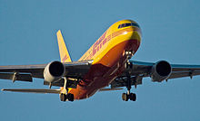 Cropped photo of a yellow and red 767 preparing to land. Undercarriage are extended. One engine is hung beneath each of the two wings.