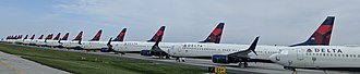Many in line airplanes with the Delta Air Lines logo on the tail, parked on pavement behind a fence.