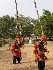 två män, klädd i en hög krönad mask, dansar på ett sandigt område