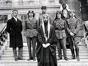 "McMahon–Hussein Correspondence - Emir Faisal's party at Versailles, during the Paris Peace Conference of 1919. At the centre, from left to right: Rustum Haidar, Nuri as-Said, Prince Faisal, Captain Pisani (behind Faisal), T. E. Lawrence (known as ""Lawrence of Arabia""), unknown, Captain Tahsin Qadri."
