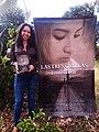 """Fennys Tovar al lado de un pendón promocional del libro """"Las Tres Orillas"""".jpg"""