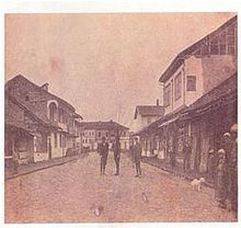 Street with three people standing in the middle