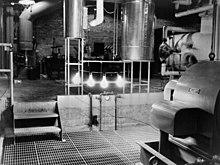 Una sala industrial con cuatro grandes bombillas iluminadas que cuelgan de una barra.