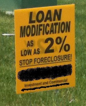 A sign advertising foreclosure rescue, name an...