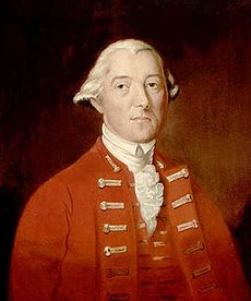 A half-height oil portrait of Carleton. He faces front, wearing a red coat and vest over a ruffled white shirt. His hair is white, and is apparently pulled back.