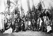 A group of rebels in traditional Arab dress posing with rifles with date palms in the background