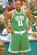 "A basketball player stands on a basketball court. He wears a green jersey with the word ""CELTICS"" and the number 11 on the front."