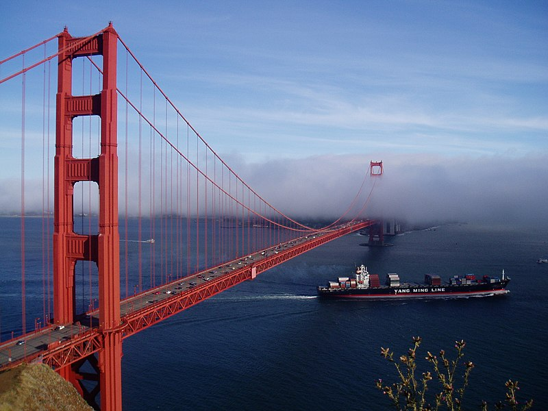 A Yang Ming ship passes under the Golden Gate Bridge. A new trend in slow-steaming at 20-22 knots means it takes three days longer to cross the Pacific Ocean.