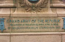 Raised copper lettering on a granite monument base.