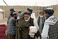 Haji Faizal Mohammad, center, the governor of the Panjwai district of Kandahar province, Afghanistan, greets a farmer during an agricultural shura, or meeting, at Combat Outpost Mushan in the province March 28 130328-A-ZZ999-901.jpg