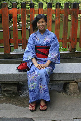 Obi (sash) - Girl wearing a yukata. A striking effect is obtained by folding the reversible obi to reveal the contrasting underside.