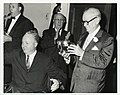 Harry Blake, President of the Greater Boston Chamber of Commerce holds a ceremonial bowl next to Mayor John F. Collins as an unidentified man applauds in the background (12461968503).jpg