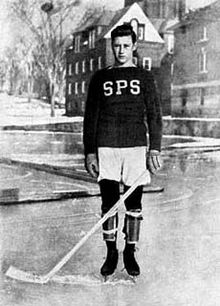 "Black and white photo of a young boy posing on an ice rink. He is wearing skates and gloves, while holding a hockey stick. He's wearing a sweater with the letters ""SPS"" on it"