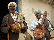A pair of Indian folk musicians performing in a rural village
