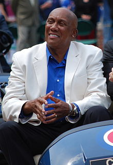 A smiling, dark-skinned man wearing a white suit jacket, a blue button-down shirt and dark pants