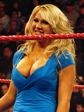 A blond, Caucasian woman stands in a wrestling ring, while wearing a blue top and smiling. A red ring rope is visible in front of her.