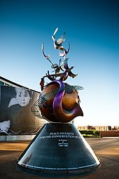 A colour photograph of a large metal monument with a conical base supporting a globe that is wrapped in contorted musical instruments. In the background is a blue sky.