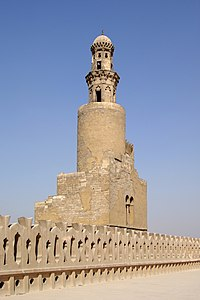 Photo of a minaret in four levels, with battlements in the foreground