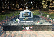 "A large rock set on a pedestal of polished stone. On the pedestal, the words ""Katyn Memorial"" are visible. On the rock, a plaque reads ""In memory of 25,000 Polish prisoners of war and professional classes who were killed on Stalin's orders by the Soviet Secret Police in 1940 at Katyn Forest, Kharkov, Miednoye, Kozielsk, Starobielsk, Ostaszkov and elsewhere. Finally admitted in 1990 by the USSR after 50 years of shameful denial of the truth."""