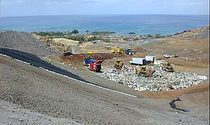 """Landfill operation. Note that the area being filled is a single, well-defined """"cell"""" and that a rubberized landfill liner is in place (exposed on the left) to prevent contamination by leachates migrating downward through the underlying geological formation."""