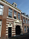 foto van Drie traveeën breed pand waarvan de pui is opgeofferd aan ingangsportaal van de Noorderkerk