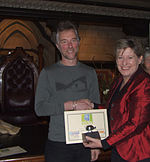 Minister Lianne Dalziel shaking Robert Ibell's hand and holding a certificate and a trophy