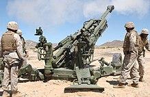 Marsoldatoj kolektas ĉirkaŭ M777-bombardilo, dum la fumo de ĵus pafita rondo restadas