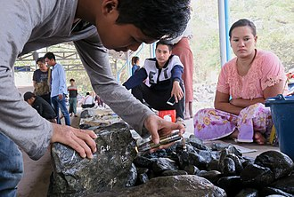 Jade - Jade rock inspection with a portable UV LED torch in Mandalay Jade Market.